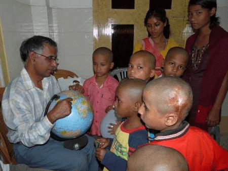 Bishal, vorne rechts im Jahr 2009. Der Gründer und ehemalige Heimleiter Fr. Lukose zeigt den Kindern wo der Besuch aus Deutschland herkommt. Die Haare der Kinder? Kurzer Prozess nach einem Läusebefall…