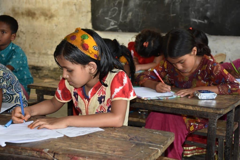 Mädchen bei den Schulaufgaben in Kurigram Bangladesch