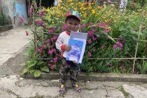 Junge erhält Lernpaket Nepal